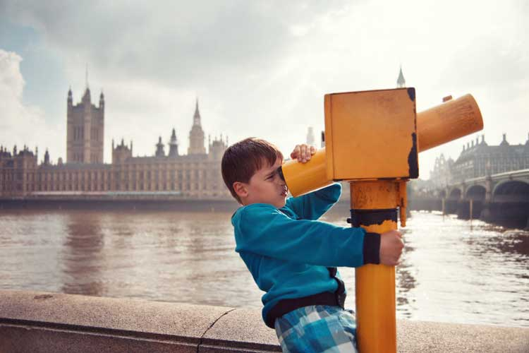 A boy looking through a telescope with the Houses of Parliament in the background.