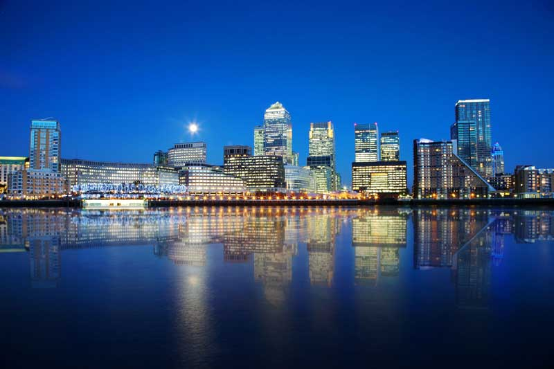 A view of Canary Wharf and other Docklands buildings by night.