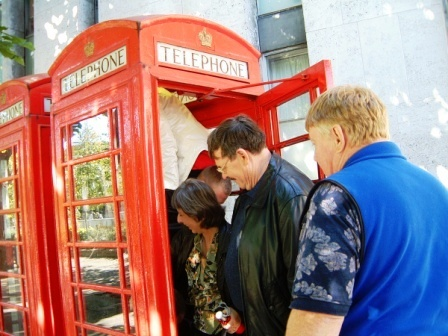 Group entering a phone box and the Harry Potter Walk of London.