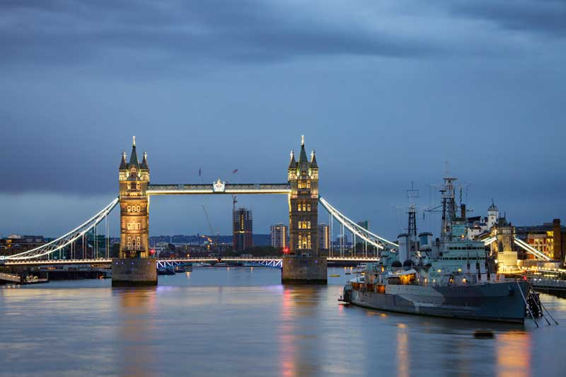 Tower Bridge and HMS Belfast seen by night.