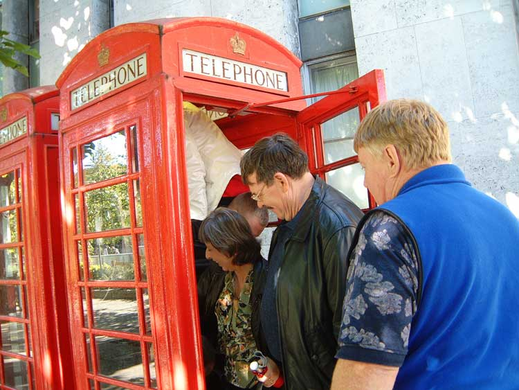 People getting into a phone box.