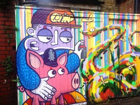 A pig wearing a policeman's helmet that is painted on a wall of Brick Lane in East London.