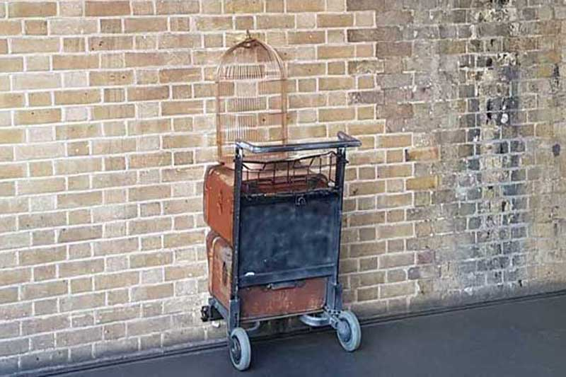 A trolley embedded in the wall of Platform nine-and-three-quarters at King's Cross Station.