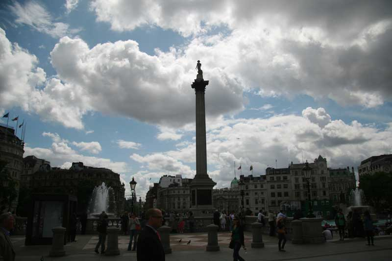 A view of Trafalgar Square with dark clouds overhead.